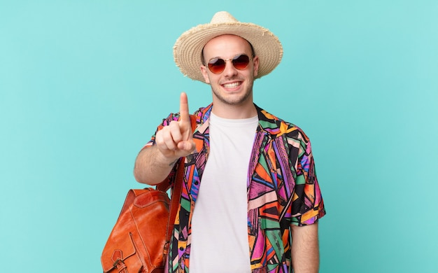 Touristischer mann, der stolz und selbstbewusst lächelt und die nummer eins triumphierend posiert und sich wie ein anführer fühlt