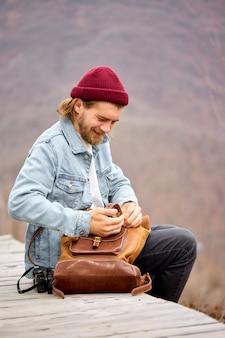 Touristischer mann, der während der wanderung in den bergen nach dingen in braunem lederrucksack sucht.