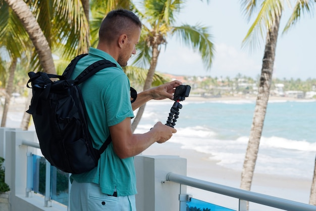 Touristischer mann mit rucksack machen blog in der küste am sonnigen tag. mann, der zeit am meer verbringt. sommerferien, reiseblog-konzept.