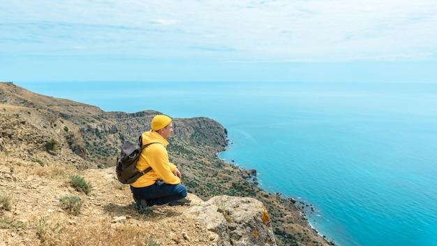 Touristischer mann mit rucksack sitzt auf der spitze des berges und genießt die schöne aussicht auf das meer. sommerreisekonzept