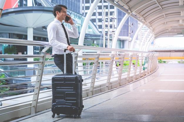 Touristischer reisender des geschäfts mit gepäck benutzt seinen handy