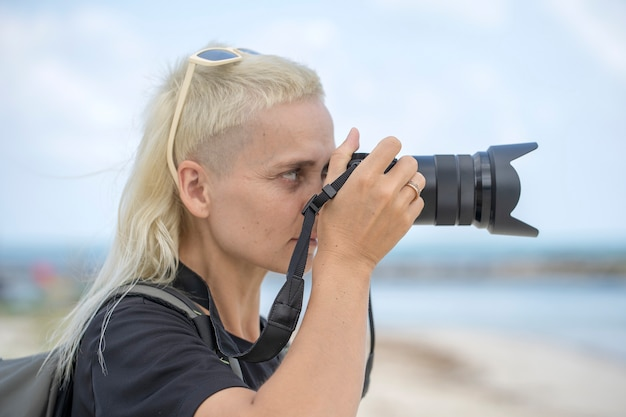 Touristischer reisender fotograf, der landschaftsaufnahmen auf der fotokamera macht, hipster-mädchen mit rucksack, die schöne meereslandschaft genießen. nahaufnahme porträt junges blondes mädchen mit rucksack am strand