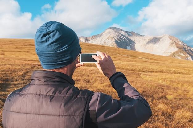 Touristischer reisender fotografiert die berge, die mit wolken auf einem smartphone bedeckt werden