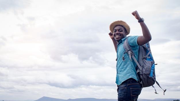 Touristischer reisendmann des erfolgs afrikanischer mit rucksack auf ansicht des berges