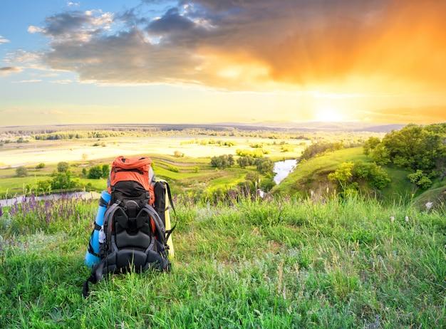 Touristischer rucksack auf hügel über fluss bei sonnenuntergang