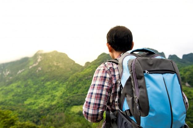 Touristischer wanderer, der schöne ansicht des grünen tropischen berges betrachtet
