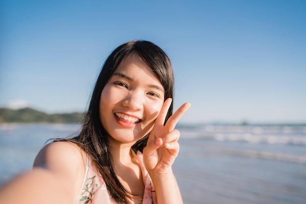 Touristisches asiatin selfie auf strand, junges schönes weibliches glückliches lächeln unter verwendung des handys, der selfie nimmt
