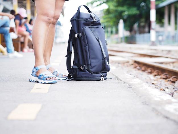 Touristisches bein der frau, das auf den zug an der plattform steht und wartet