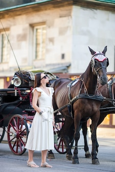 Touristisches mädchen, das einen spaziergang durch wien genießt und die schönen pferde im wagen betrachtet