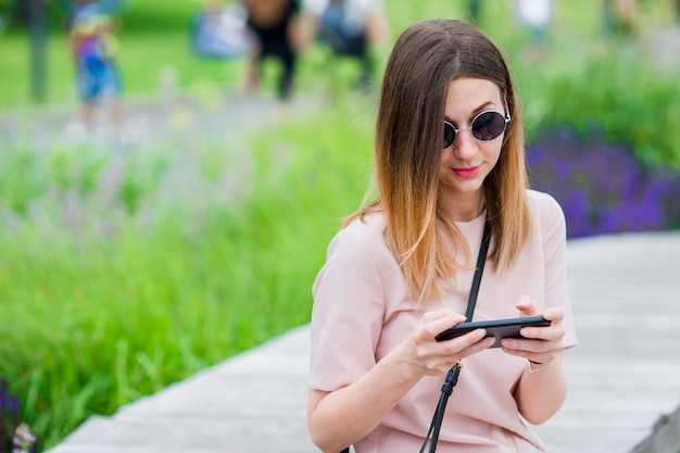 Touristisches mädchen, das messgae durch smartphone an den sommerferien sendet. junge attraktive frau mit handy feiertagsreiseziel im tourismus draußen genießend und konzept erforschend