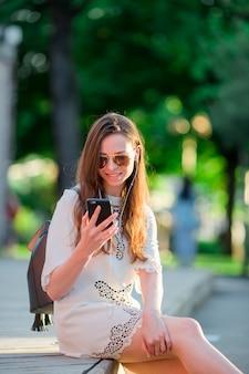 Touristisches mädchen, das messgae durch smartphone an den sommerferien sendet. junger attraktiver tourist mit handy feiertagsreiseziel im tourismus draußen genießend und konzept erforschend
