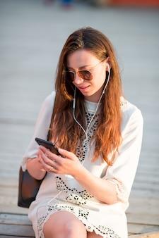 Touristisches mädchen, das mitteilung durch smartphone an den sommerferien sendet. junge attraktive frau mit handy feiertagsreiseziel im tourismus draußen genießend und konzept erforschend