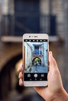 Touristisches mädchen, das reisefotos mit smartphone an den sommerferien macht.