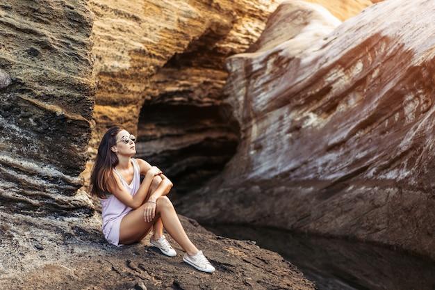 Touristisches mädchen des recht langen haares brunette, das auf den steinen sich entspannt, nähern sich meer.