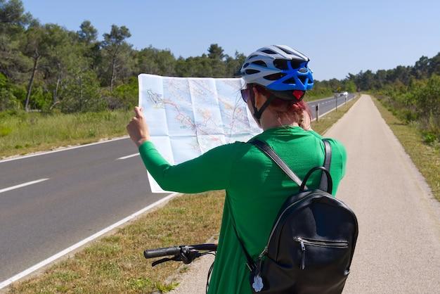 Touristisches mädchen in einem helm auf einem fahrrad, das eine karte an der kreuzung von fahrradstraßen untersucht