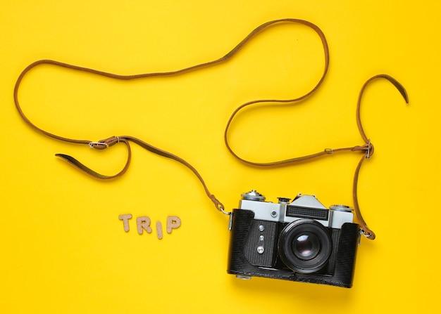 Touristisches minimalismuskonzept. vintage retro-filmkamera im lederbezug mit gurt auf gelb mit wortreise.