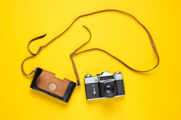 Touristisches minimalismuskonzept. vintage retro filmkamera und lederbezug mit riemen auf gelb.