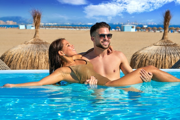 Touristisches paarbad im infinity-pool am strand