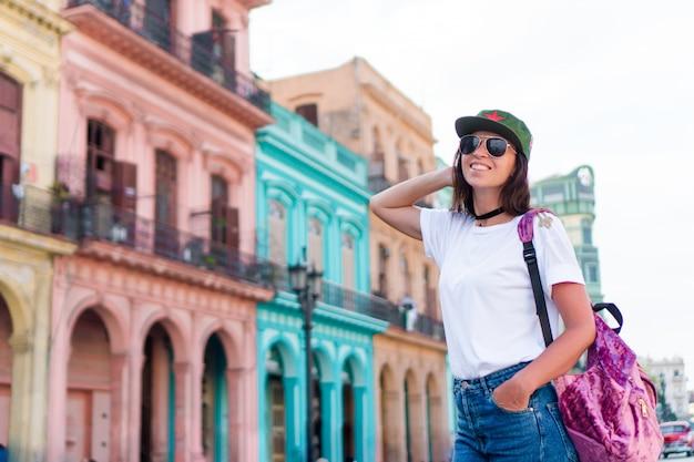 Touristisches schönes mädchen im populären bereich in altem havana, kuba. reisendlächeln der jungen frau glücklich.