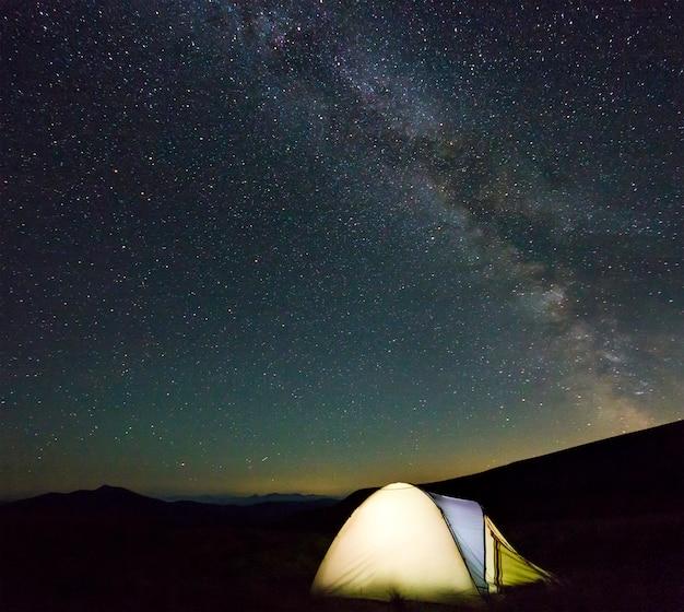 Touristisches wandererzelt in den bergen nachts mit milchstraßesternen im himmel