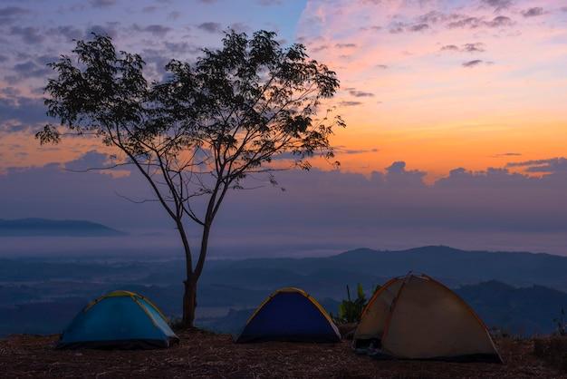Touristisches zelt im lager unter wiese im berg bei sonnenaufgang