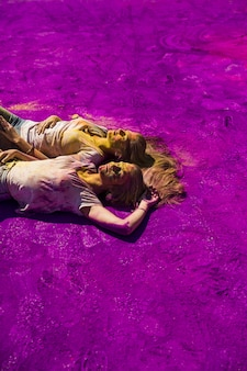 Tow junge frau, die auf purpurroter holi farbe sich entspannt