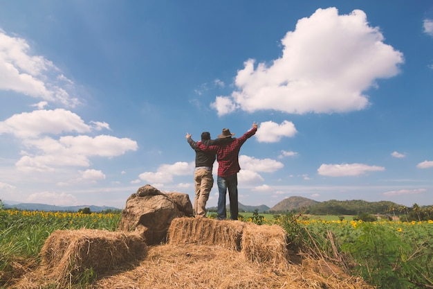 Tow man celebration success-glück auf einem steinabend-himmel-sonnenuntergang