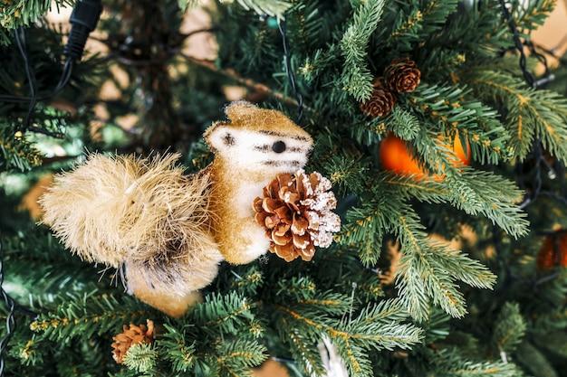 Toy christmas orange flauschige eichhörnchen mit kegelnahaufnahme sitzt auf dem weihnachtsbaum
