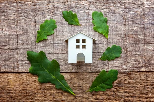 Toy house und grüne eichenblätter auf holztisch
