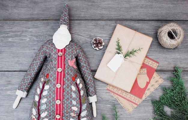 Toy santa claus im mantel in der nähe von präsentkarton, fäden und zweigen