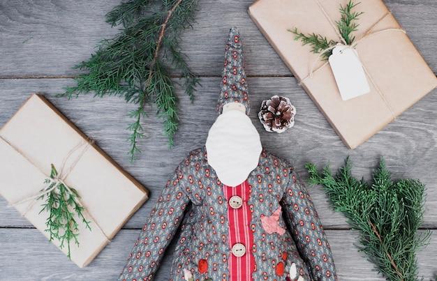 Toy santa claus im mantel zwischen präsentkartons und zweigen