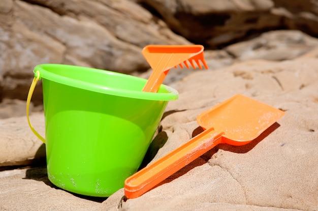 Toys strand im sand in den farben orange und grün