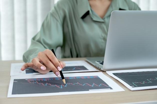 Trader geschäftsfrau hand mit bleistift, aktiendiagramm analysieren gesetzte ziele für den online-forex-handel.