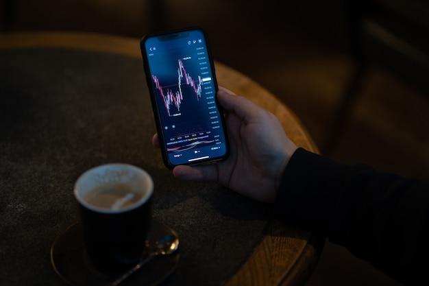 Trader oder investor, der finanznachrichten liest und echtzeit-börsendaten analysiert, während er im freien sitzt und kaffee trinkt, männliche hand, die smartphone mit live-forex-chart auf dem bildschirm hält