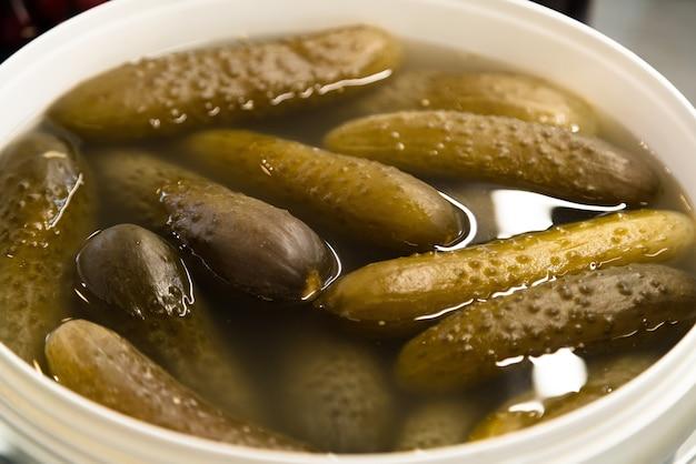 Traditionell eingelegte gurken im eimer in eigener salzlake.