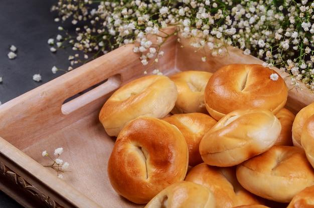 Traditionell von selbst gemachten brötchen mit frischen gebackenen brötchen über dem hölzernen