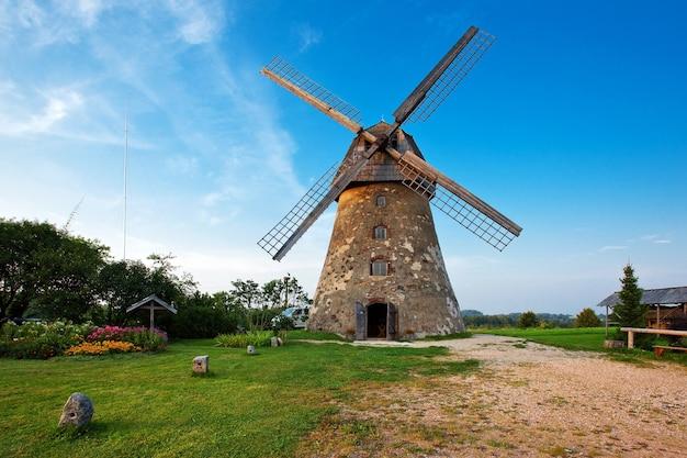 Traditionelle alte holländische windmühle in lettland gegen blauen himmel mit weißen wolken