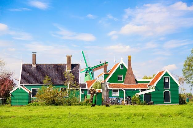 Traditionelle alte holländische windmühle mit alten häusern gegen blauen bewölkten himmel im dorf zaanse schans, die niederlande.