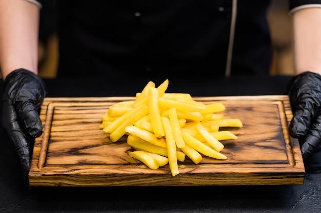 Traditionelle amerikanische fastfood-restaurantsnacks. abgeschnittene aufnahme des kochs, der eine portion pommes auf einem holzbrett hält.