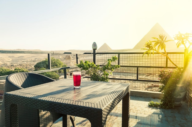 Traditionelle arabische kräutertee-karkade in einem glas vor dem hintergrund der großen pyramiden von gizeh. schöne aussicht auf die attraktion im restaurant.