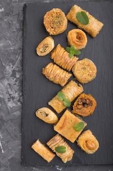 Traditionelle arabische süßigkeiten (kunafa, baklava) auf einem schwarzen schieferbrett auf einem schwarzen betonhintergrund.