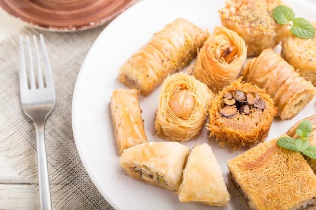 Traditionelle arabische süßigkeiten (kunafa, baklava) und eine tasse kaffee auf einem weißen hölzernen hintergrund. seitenansicht, selektiver fokus.