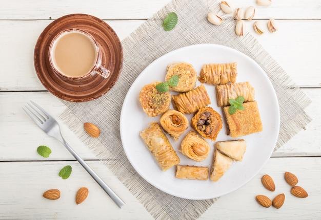 Traditionelle arabische süßigkeiten (kunafa, baklava) und eine tasse kaffee. draufsicht, nahaufnahme.