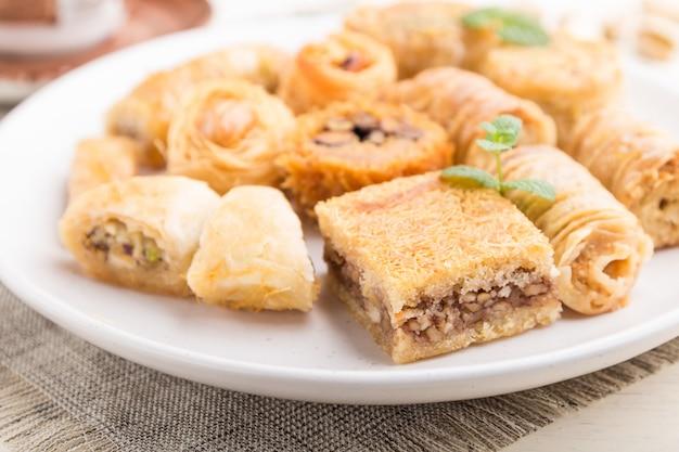 Traditionelle arabische süßigkeiten (kunafa, baklava) und eine tasse kaffee. seitenansicht