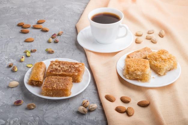 Traditionelle arabische süßigkeiten und eine tasse kaffee. seitenansicht, nahaufnahme.