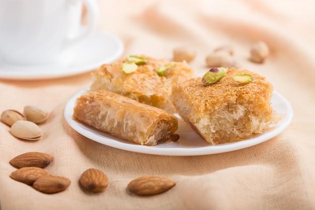 Traditionelle arabische süßigkeiten und eine tasse kaffee. seitenansicht