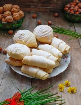 Traditionelle aserbaidschan-feiertagsplätzchen und -süßigkeiten auf weißer platte auf dem rustikalen mit nüssen