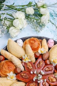 Traditionelle aserbaidschanische feiertags-novruz-kekse baklavas und shakarburas auf schwarzem tablett teller auf tisch