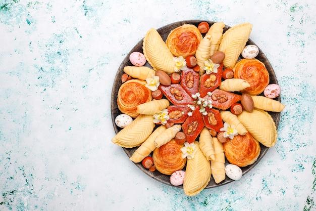 Traditionelle aserbaidschanische feiertags-novruz-kekse baklavas und shakarburas auf schwarzem tablettteller auf licht