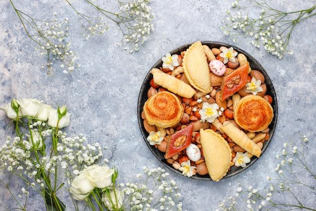 Traditionelle aserbaidschanische feiertags-novruz-kekse baklavas und shakarburas auf schwarzer tablettplatte auf dem grauen betonhintergrund